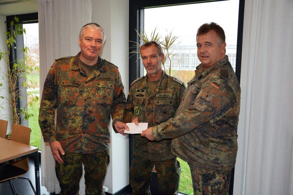 Das Bild zeigt BrigGen Krogmann und Oberstlt Wagner bei der Übergabe der Spende an StFw Buchner