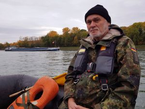 Der Stabsunteroffizier Heinz Cecil befindet sich mit einem Sturmboot der Bundeswehr auf dem Rhein. Im Hintergrund ist ein Binnenschiff zu sehen.